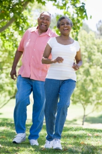 Active adult couple walking in park